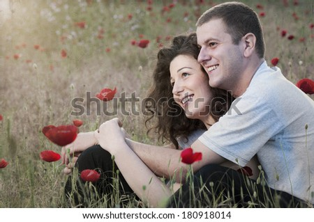 Young happy couple hugging each other in field of poppy flowers  - stock photo