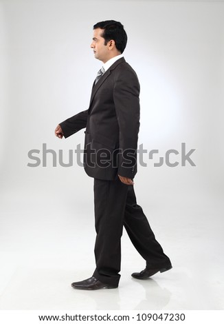 young indian business man walking on background - stock photo