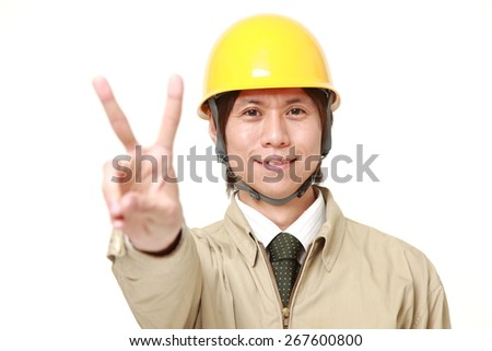 young Japanese construction worker showing a victory sign - stock photo