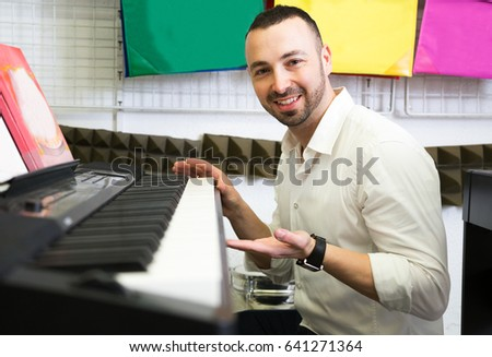 Young man customer selecting synthesizer in store and smiling