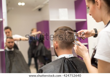 young man cuts hair in the beautiful barber shop - stock photo