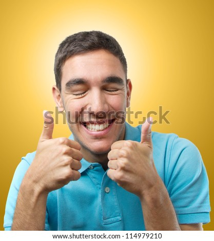 Young man doing the double ok sign over light orange gradient - stock photo