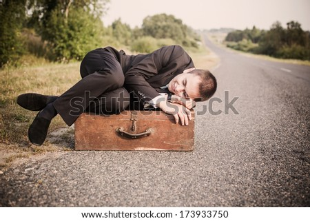 young man lies on the old suitcase on the road - stock photo