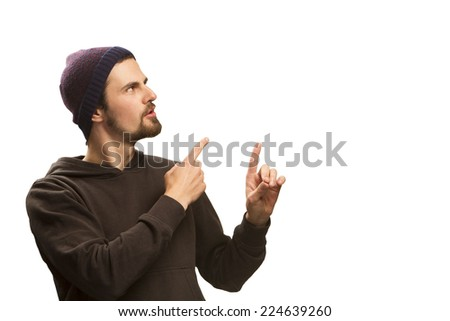 young man pointing with bouth hands to the side and looking there, surprised. bearded. European. against white background. With copy space.  - stock photo