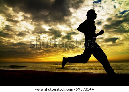 young Man runs at the beach on beautiful summer sunset