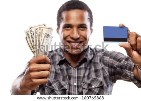 young man showing credit card and money in the other hand - stock photo