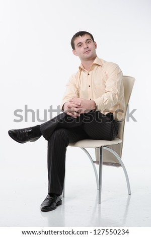 Young man sitting on white chair isolation on white. - stock photo