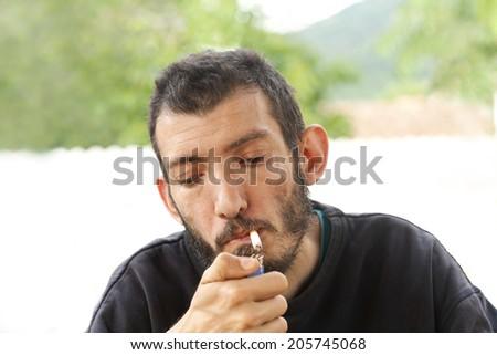 Young man smoking a cigarette - stock photo