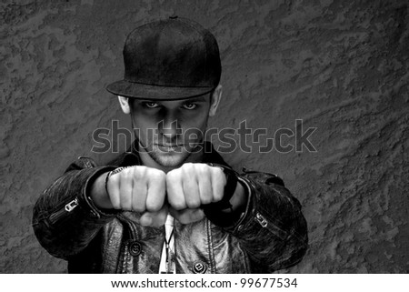 young man stares into the camera thrusting his fists - stock photo