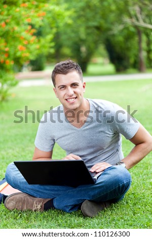 Young man using his laptop on the grass - stock photo