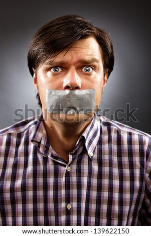 Young man with duct tape over his mouth against gray background. Conceptual image - stock photo