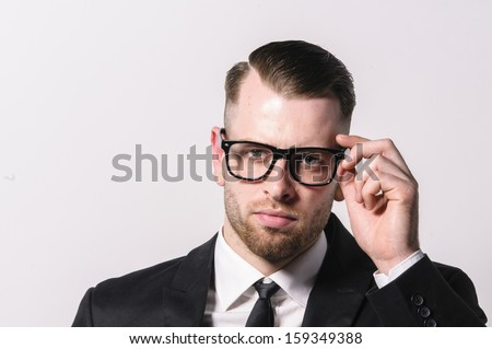 Young man with short hair and stubble wears a dark suit and a narrow tie. He holds his hand to his glasses. - stock photo