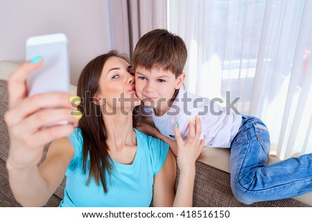 Young mother and her son taking a selfie on the sofa.Happy family. - stock photo