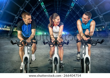 Young people  doing spinning on cycle bike - stock photo