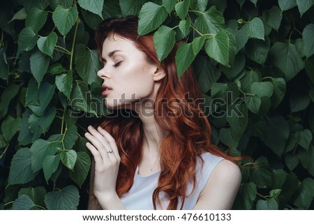 young red-haired woman in a park closed her eyes and touches the foliage