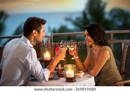 Young , romantic couple toasting during dinner  on tropical resort  - stock photo