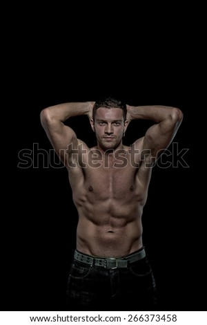 Young sexy handsome athletic man with naked torso on black  background with copyspace - stock photo