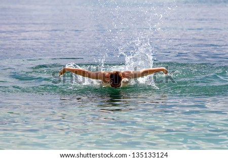 young sporting man swims in the sea dolphin style.