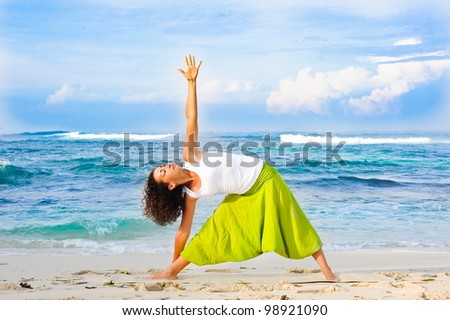Young sporty girl doing yoga on the beach - stock photo