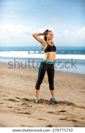 young sporty woman stretching  on beach