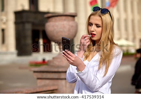 Young stylish woman applying lipstick  against summer urban background.