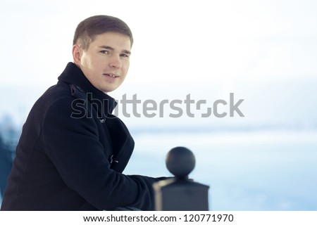 Young the man costs on winter quay - stock photo
