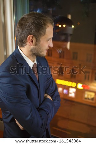 Young the man looks out of the window at night - stock photo