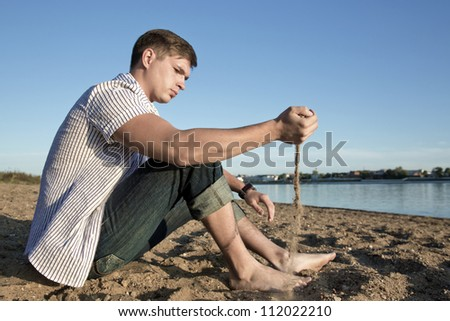 Young the man sits on coast - stock photo