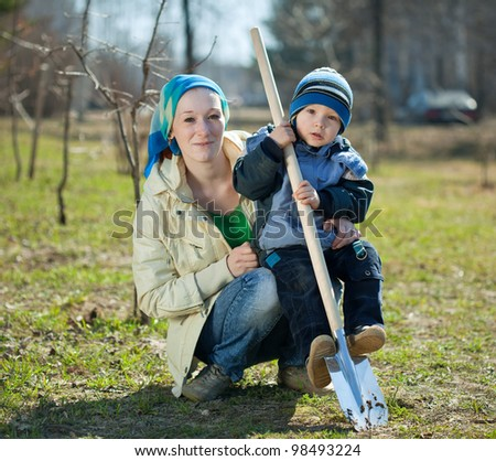 young woman and boy  spading with spade in garden - stock photo