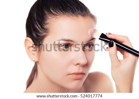 Young woman applying make up face nude close