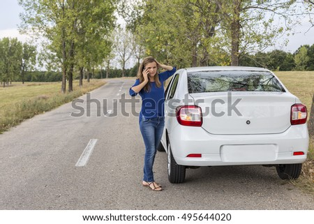 Young woman calling for assistance  next to a broken down car parked on the side of a road