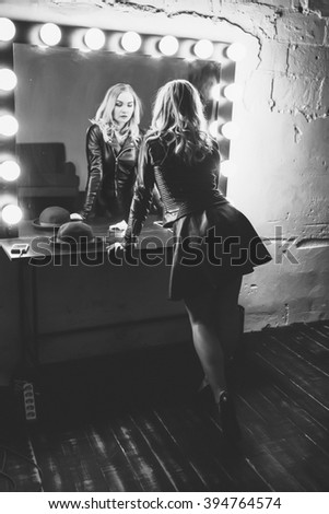 Young woman doing makeup , old-fashioned. Stands near  mirror. Backstage.