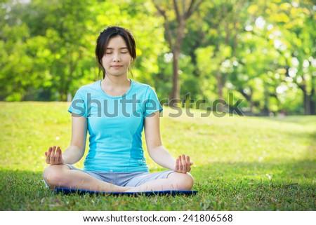 Young Woman doing Yoga Exercises,Jaladharabandha pose, Outdoor - stock photo