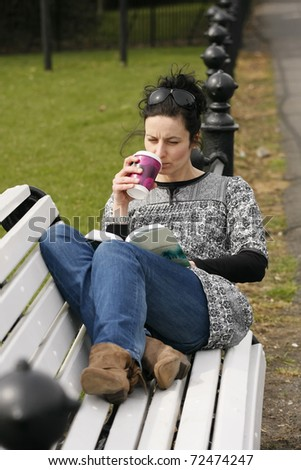 30-35 young woman drinks coffee and reads novel on bench in public place - stock photo