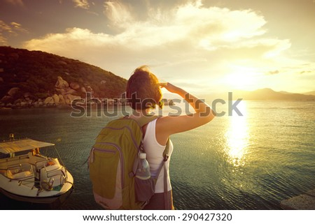 Young woman hiker standing on the coast and enjoying sunrise over the sea. Traveling along Asia, active lifestyle concept
