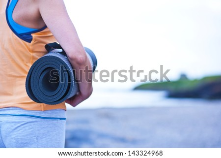 young woman holding a yoga mat - stock photo