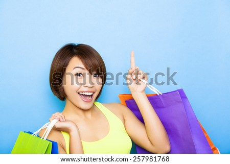 young  woman holding shopping bags and pointing up - stock photo