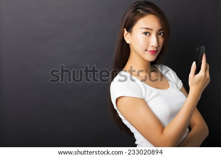 young woman holding smart phone with black background - stock photo