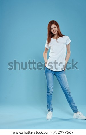 young woman in a white T-shirt in jeans in full growth on a blue background, studio