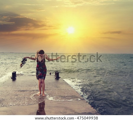young woman in dress barefoot walking the pear near the Sea at sunrise