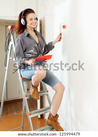 young woman in headphones with roller on stepladder in the interior