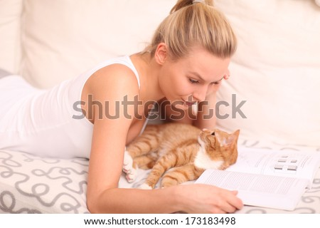 young woman lying on a sofa with her cat and reading a book  - stock photo
