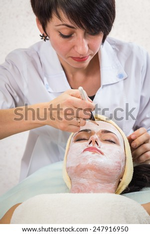 Young woman receiving facial mask at beauty salon - stock photo
