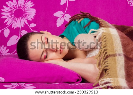 Young woman sleeping with a toy. Healthy Sleep. Sweetly sleeping beautiful girl brunette, covered with warm blanket. - stock photo