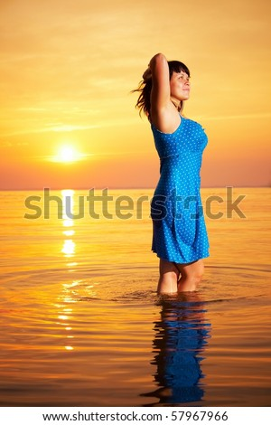 Young woman standing in  water at sunset - stock photo
