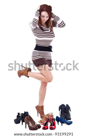 young woman surrounded by shoes, isolated on white - stock photo