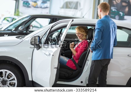 young woman test new model in the  car dealership saloon - stock photo