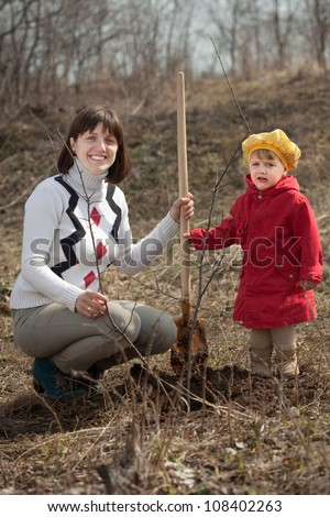young woman with  little daughter sets tree  in spring