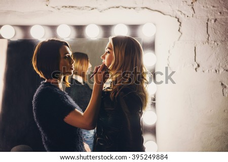 Young women doing makeup , old-fashioned. Stands near  mirror. Backstage. - stock photo