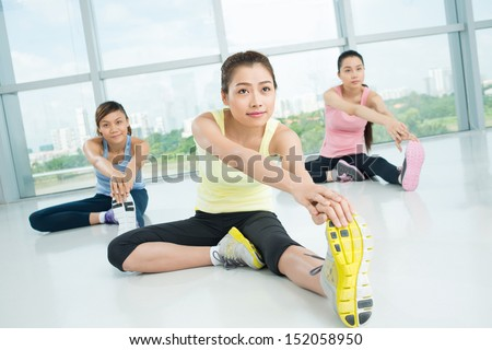 Young women doing stretching exercises in the aerobics class on the foreground  - stock photo